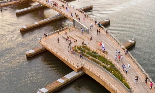 Curved pedestrian bridge links two riverfront parks in Providence